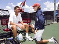 Coach sportif ou entraîneur auprès d'un joueur de tennis sur le court