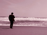 Homme en costume, seul sur la plage face à la mer
