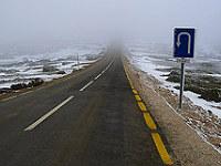 Route dans un paysage enneigé et panneau demi-tour