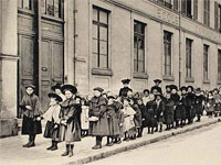 Ecoliers en rang devant une école, photo prise vers 1900
