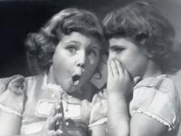 Une fillette chuchote dans l'oreille d'une autre