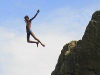 Enfant sautant d'un rocher en maillot