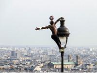 Artiste perché en haut d'un lampadaire avec un ballon en équilibre sur le front