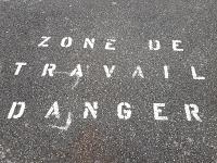 """Sur le trottoir, inscription """"Zone de travail danger"""""""