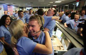 Ingénieur congratulant une collègue après atterrissage réussi de la sonde sur Mars, août 2012