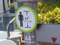 Panneau indiquant la taille minimale avant l'entrée d'un manège