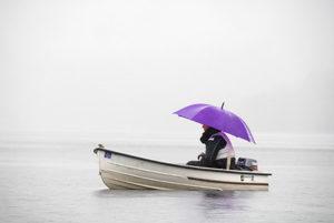 Femme avec parapluie dans une barque sur l'eau