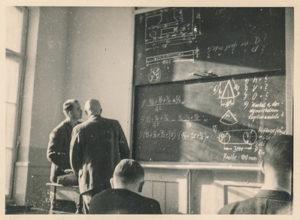 Etudiants devant un tableau noir plein d'équations